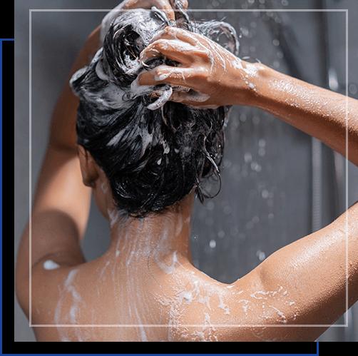 Kobieta myje wlosy szamponem przeciwlupiezowym